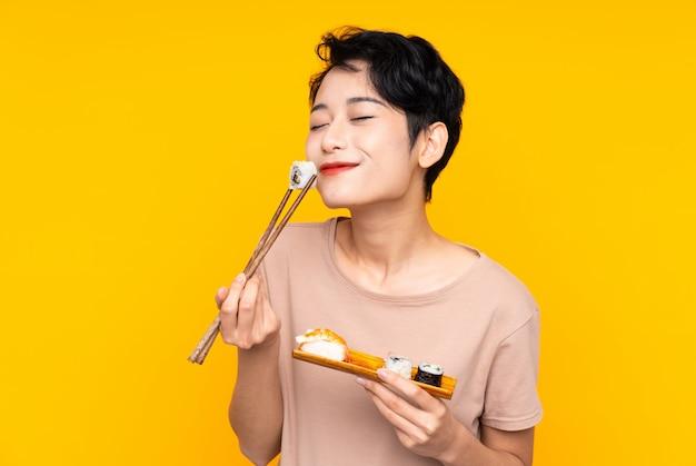Jonge aziatische vrouw met sushi