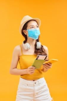 Jonge aziatische vrouw met telefoon, paspoort en gezichtsmasker voor bescherming coronavirus over oranje achtergrond.
