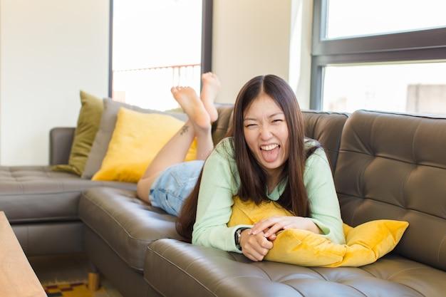 Jonge aziatische vrouw met vrolijke, zorgeloze, rebelse houding, grappen maken en tong uitsteken, plezier maken