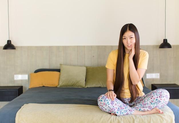 Jonge aziatische vrouw met wang en pijnlijke kiespijn, zich ziek, ellendig en ongelukkig voelen, op zoek naar een tandarts