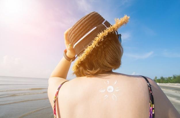 Jonge aziatische vrouw met zonnebrandolie op het strand op zonnige dag