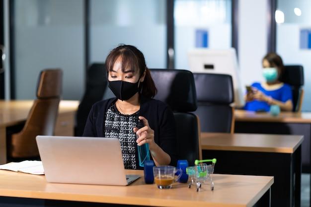 Jonge aziatische vrouw officier desinfecterende spray op doekjes schoonmaken laptop computer op bureau kantoor tegen coronavirus covid-19