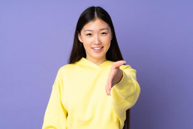 Jonge aziatische vrouw op purpere muur het schudden handen voor heel het sluiten
