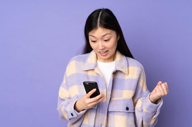 Jonge aziatische vrouw op purpere muur verrast en het verzenden van een bericht