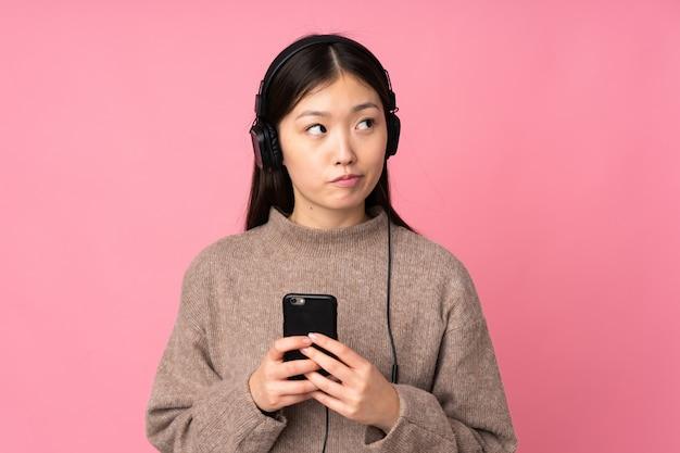 Jonge aziatische vrouw op roze muur het luisteren muziek met mobiel en het denken