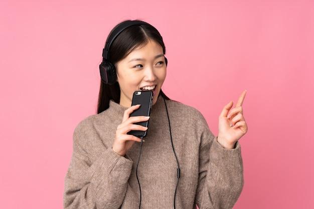 Jonge aziatische vrouw op roze muur het luisteren muziek met mobiel en het zingen