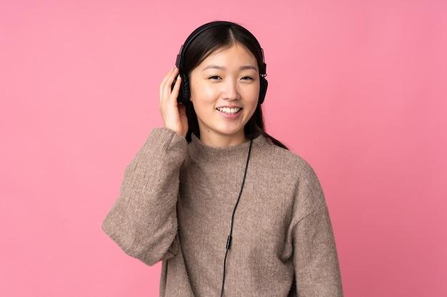 Jonge aziatische vrouw op roze muur luisteren muziek