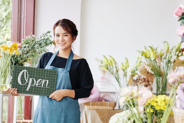 Jonge aziatische vrouw opening bloemenwinkel