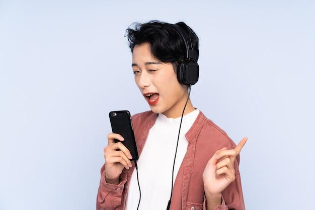 Jonge aziatische vrouw over geïsoleerde blauwe muur het luisteren muziek met mobiel en het zingen