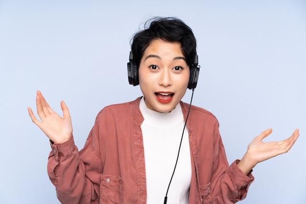 Jonge aziatische vrouw over geïsoleerde blauwe surpeised muur en het luisteren muziek