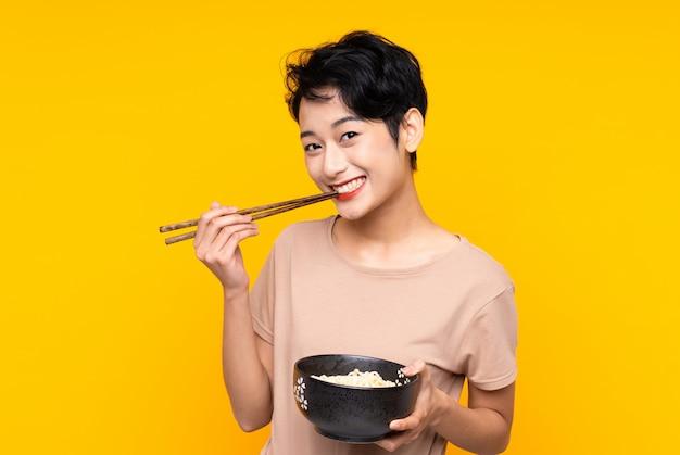 Jonge aziatische vrouw over geïsoleerde gele muur die een kom van noedels met eetstokjes houdt