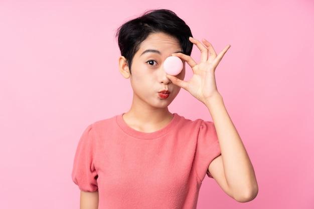 Jonge aziatische vrouw over geïsoleerde roze muur die kleurrijke franse macarons met grappig gezicht houdt