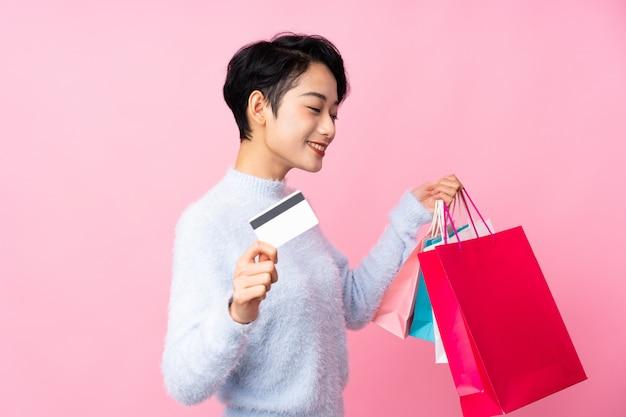 Jonge aziatische vrouw over geïsoleerde roze muurholding het winkelen zakken en een creditcard