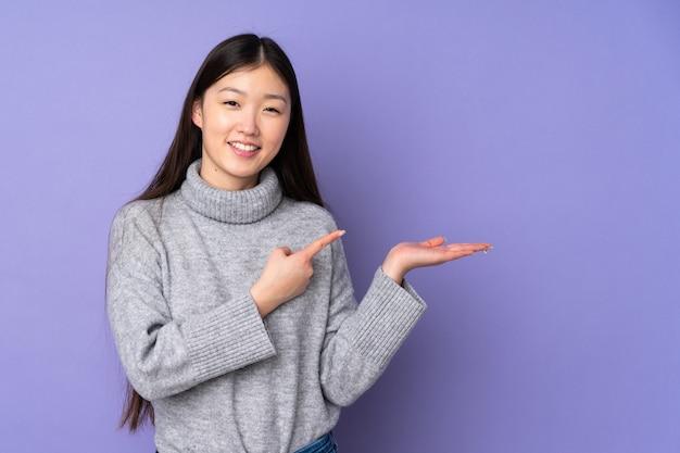 Jonge aziatische vrouw over geïsoleerde ruimteholding copyspace denkbeeldig op de palm om een advertentie op te nemen