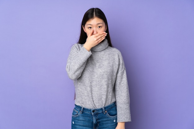 Jonge aziatische vrouw over muur die mond behandelen met hand