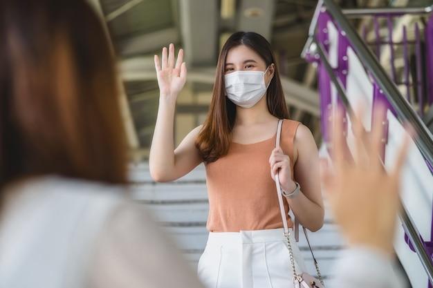 Jonge aziatische vrouw passagier met chirurgisch masker en zwaaiende hand voor groet