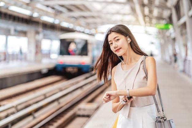 Jonge aziatische vrouw passagier muziek luisteren via slimme mobiele telefoon en trein kijken