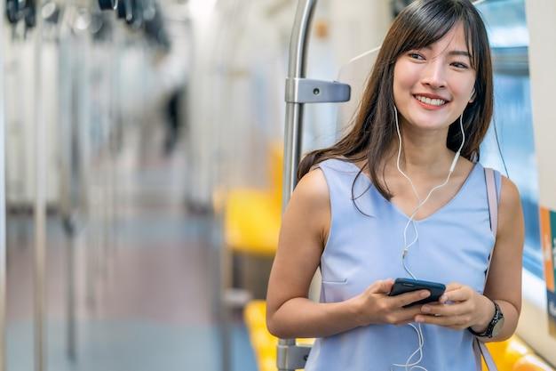 Jonge aziatische vrouw passagier muziek luisteren via slimme mobiele telefoon in metro