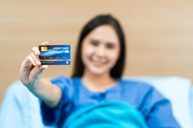 Jonge aziatische vrouw patiënt bedrijf mock-up gezondheid creditcard. ziektekostenverzekering concept