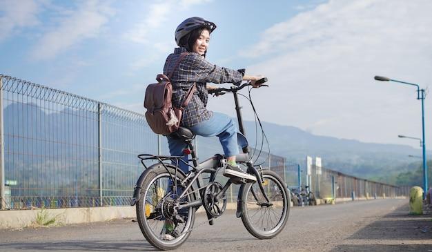 Jonge aziatische vrouw pauzeert de fiets voordat ze naar het werk gaat