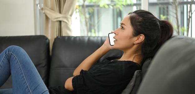 Jonge aziatische vrouw praat op een mobiele telefoon terwijl ze op de zwarte leren bank ligt