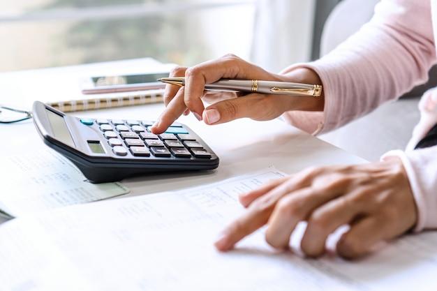 Jonge aziatische vrouw record van inkomsten en uitgaven aan haar bureau. huisbesparende concept. detailopname