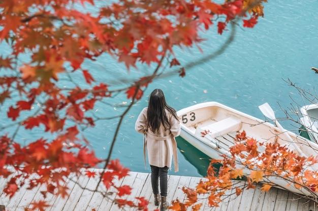 Jonge aziatische vrouw reiziger genieten van het uitzicht op rood esdoornblad op goshikinuma of vijf gekleurde vijver in de herfst in de prefectuur fukushima, japan