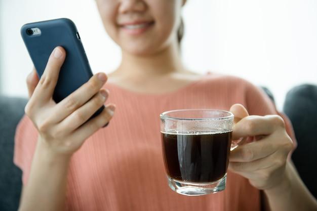 Jonge aziatische vrouw sms't en verkent sociale media op een smartphone terwijl ze 's ochtends koffie drinkt. jonge vrouw die 's ochtends een kopje koffie drinkt.