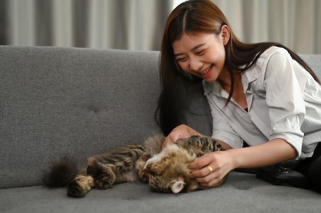 Jonge aziatische vrouw speelt met haar kat