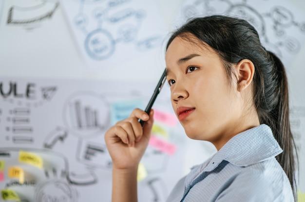 Jonge aziatische vrouw staat en denkt na over het presenteren van het schaven van het project aan boord in de vergaderruimte, kopieer ruimte