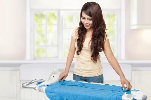 Jonge aziatische vrouw strijken