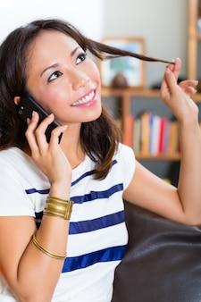 Jonge aziatische vrouw thuis op de bank