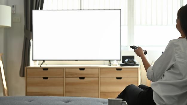 Jonge aziatische vrouw thuis tv-kijken