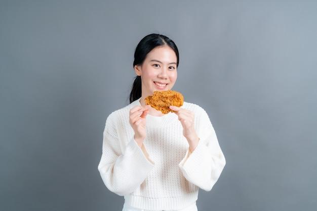 Jonge aziatische vrouw trui met blij gezicht dragen en geniet van het eten van gebakken kip