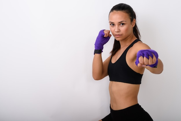 Jonge aziatische vrouw vechter met boksen wraps klaar om te vechten tegen witte ruimte