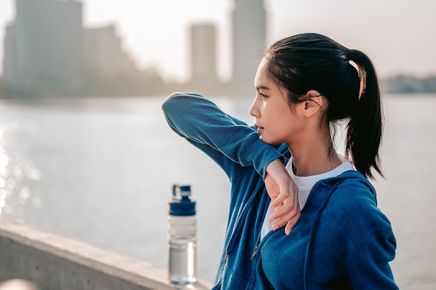 Jonge aziatische vrouw veegt zweet af na een ochtendtraining in de stad een stad die gezond leeft