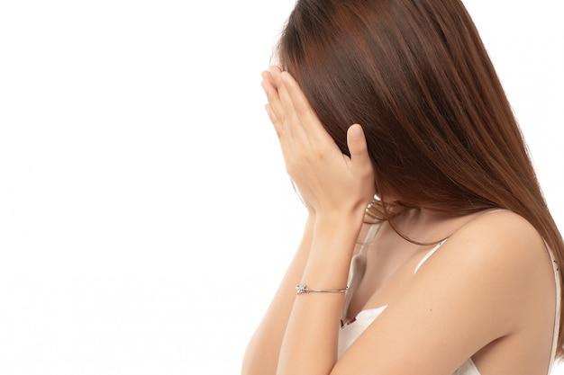 Jonge aziatische vrouw verbergt haar gezicht; mislukt meisje doet facepalm; aziatische volwassen zakenvrouw.