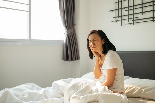 Jonge aziatische vrouw voelt kiespijn en ongemak op bed in de ochtend van de witte slaapkamer. concept van gezondheidszorg voor vrouwen. close-up beeld van jonge vrouw die lijdt aan kiespijn terwijl liggend in bed.
