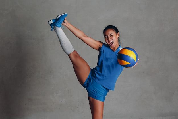 Jonge aziatische vrouw volleyballer in blauw uniform met bal