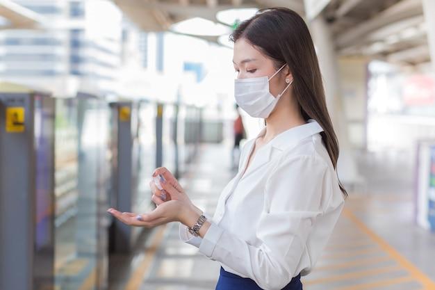 Jonge aziatische vrouw wacht op de trein op het buitenstation terwijl ze op kantoor gaat werken
