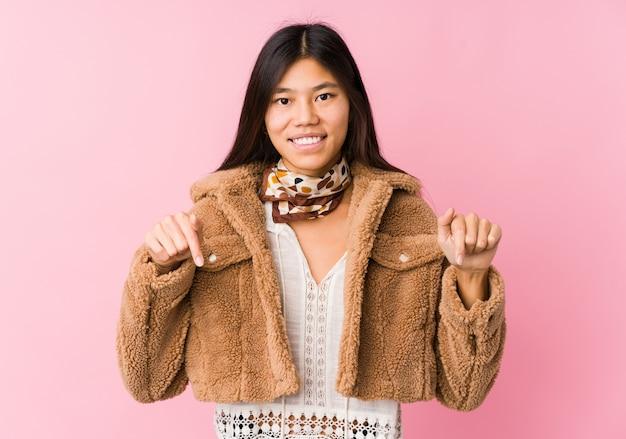 Jonge aziatische vrouw wijst naar beneden met vingers, positief gevoel.