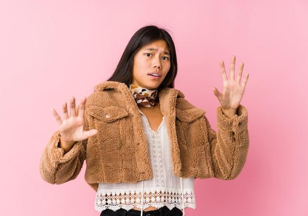 Jonge aziatische vrouw wordt geschokt vanwege een dreigend gevaar