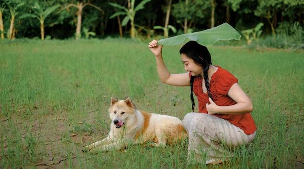Jonge aziatische vrouw zat onder een bananenblad en schuilde met een hond op de achtergrond van de groene tuin