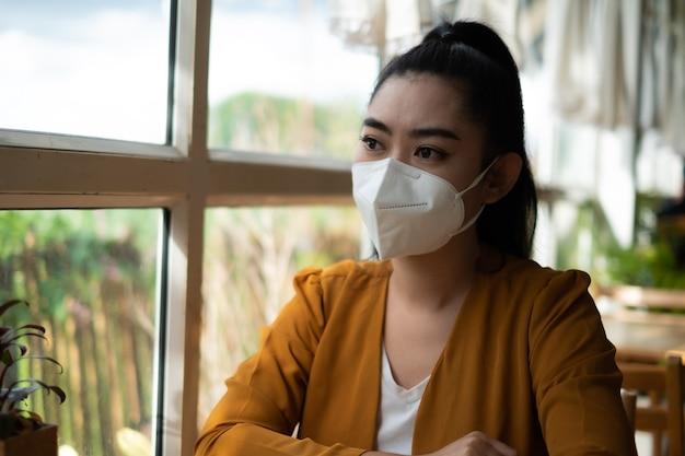 Jonge aziatische vrouw zit en zet een medisch masker op