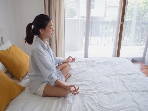 Jonge aziatische vrouw zitten en praktizeren doen yoga op bed