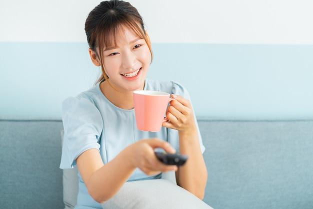 Jonge aziatische vrouw zittend op de bank, koffie drinken en televisie kijken
