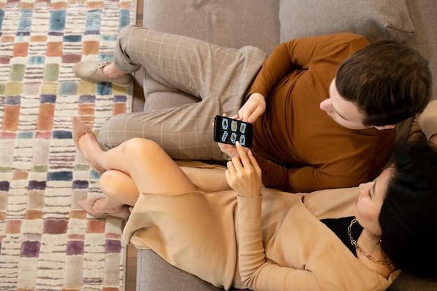 Jonge aziatische vrouw zittend op de bank naast haar man of vriend met smartphone en wijzend naar een van zulke foto's op het scherm