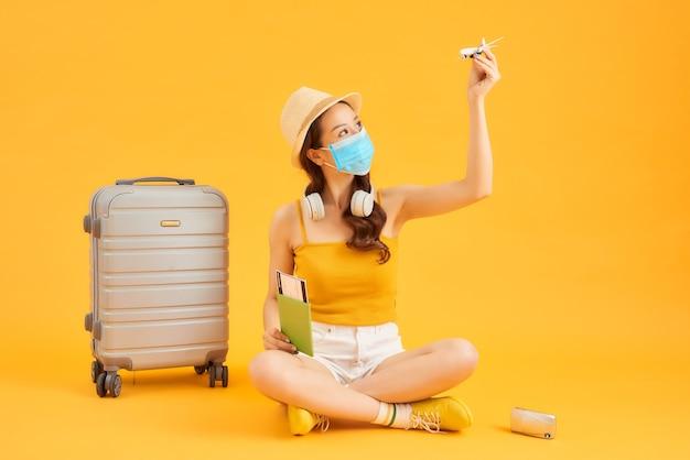 Jonge aziatische vrouw zittend op de vloer en paspoort te houden