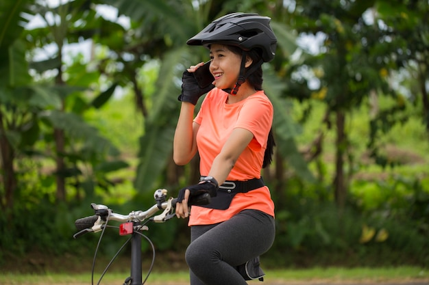 Jonge aziatische vrouw zittend op haar fiets en praten over de telefoon