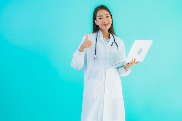 Jonge aziatische vrouwelijke arts met laptop
